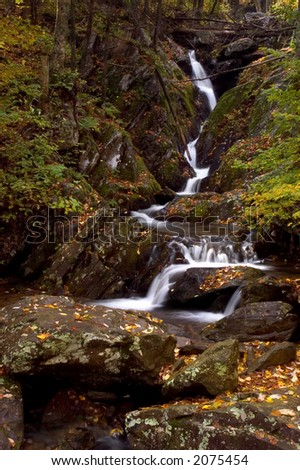 A small waterfall  in the forests of Virginia. Taken with a slow shutter speed to smooth and soften the water. The stream is framed with the leaves of autumn and laying on the moss covered boulders. - stock photo