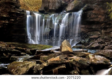 A small  waterfall in the forests of West Virginia. This one is tumbling down a steep embankment with lots of boulders to tumble over along its way. - stock photo