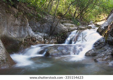 A small waterfall mountain river - stock photo