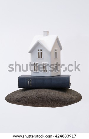 A small, white ceramic house sitting on a vintage holy bible on a big rock. A simple, abstract representation about building your life on God. Horizontal with copy space. - stock photo