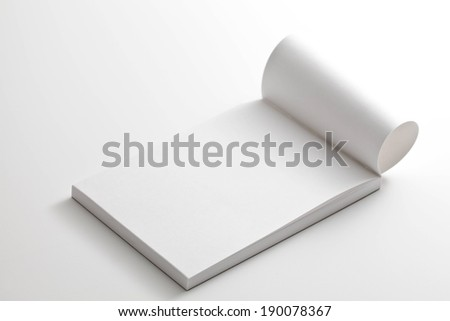 A small white notebook with a page flipped open. - stock photo