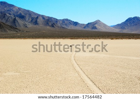 A small windblown rock moves across the Dry Lake (Playa) at the Racetrack deep in Death Valley National Park. - stock photo