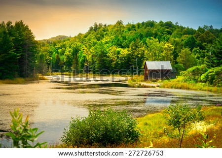 A small, wooden cabin near the edge of a small small river or pond amidst lush foliage nearing sunset. - stock photo