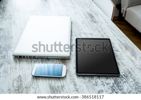 A smartphone, a tablet computer and a laptop computer on a wooden desktop.  - stock photo