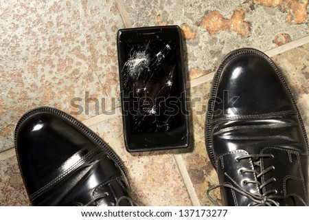 A smartphone lies broken between the shoes of its owner just after being dropped. - stock photo