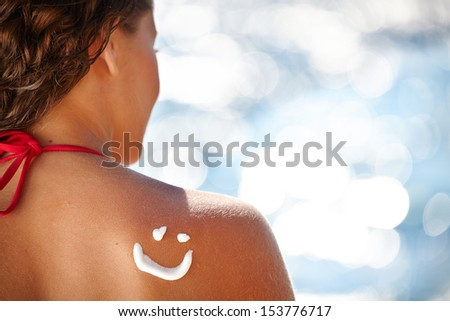 A smile made with suncream at the shoulder (shallow dof)  - stock photo