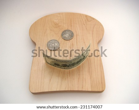 A Smiley Face Formed With Two Silver US Morgan Dollars For The Eyes And A United States Hundred Dollar Note For The Smile Resting On A Bread Shaped Cutting Board Over White With Slight Vignetting. - stock photo