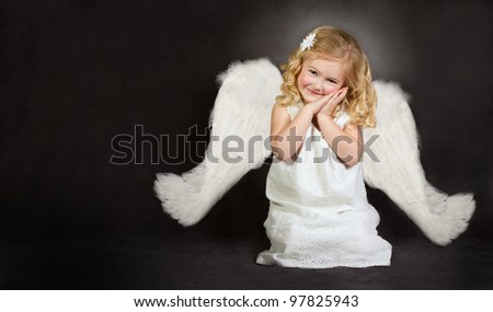 A smiling angel sitting with her hands near her face - stock photo