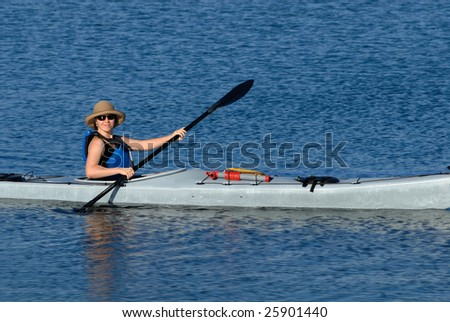 A smiling attractive young woman in sea kayak. Mission Bay, San Diego, California - stock photo