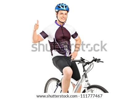 A smiling bicyclist posing on a bicycle and giving a thumb up isolated on white background - stock photo