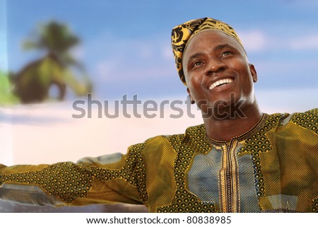A smiling black man on the beach is looking upwards - stock photo