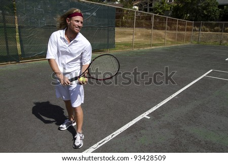 A smiling blonde male tennis player is ready to make a strong serve - stock photo