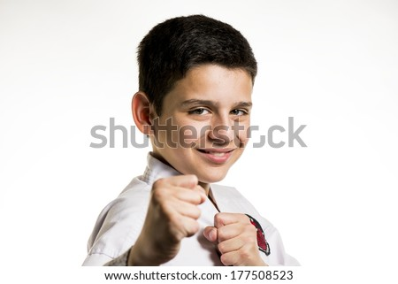 A smiling boy with his fist up in a karate fight stance. - stock photo