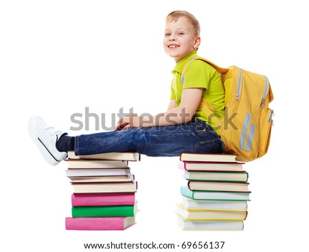 A smiling boy with satchel sitting on two heaps of books - stock photo