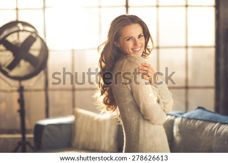A smiling brunette woman in comfortable clothing is standing in a loft living room, hugging herself while looking over her shoulder. Urban chic loft decoration details. - stock photo