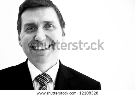 A smiling business man landscape orientation with copy space to the right. mono high contrast - stock photo