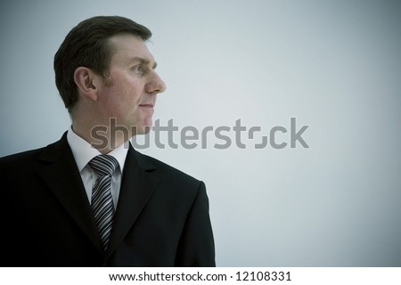 A smiling business man landscape orientation with copy space to the right. profile looking out of frame - stock photo