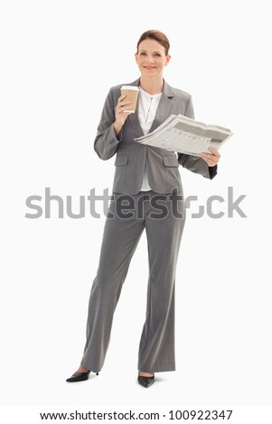 A smiling businesswoman is holding a cup and a newspaper - stock photo