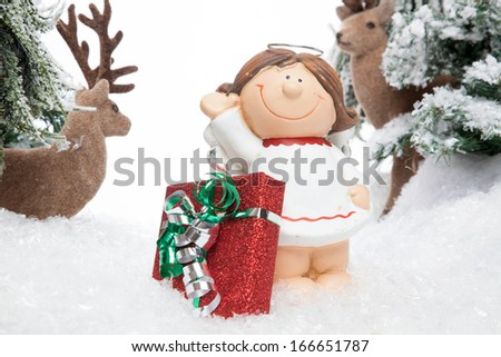 A smiling cartoon child guarded by two reindeers presents a X-Mas Gift. - stock photo