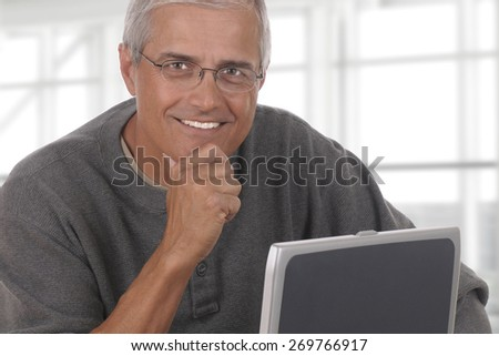 A smiling casually dressed mature businessman seated behind a laptop computer with his hand on his chin. The man is in front of a large modern office window. - stock photo
