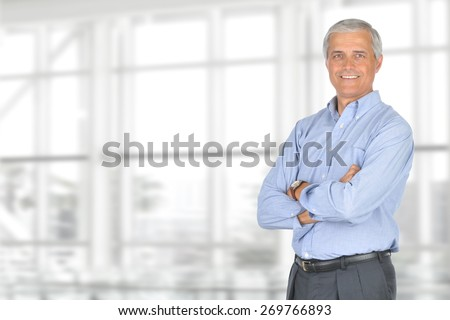 A smiling casually dressed mature businessman standing in front of a large modern office window. The man is set ot the right of the frame leaving room for your copy. Horizontal format. - stock photo