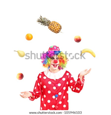 A smiling clown juggling fruits isolated against white background - stock photo