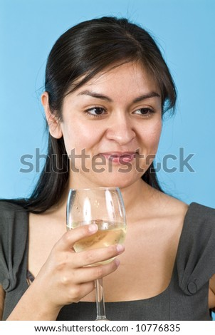 A smiling, contented, pretty young woman holding a wine glass with liquid in it. - stock photo