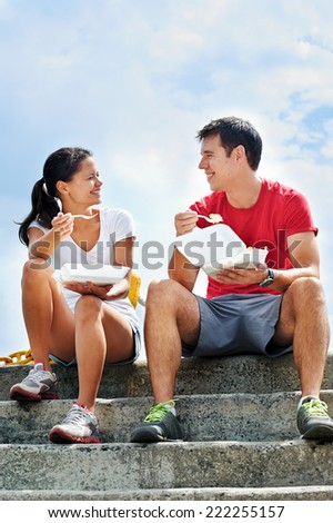 A smiling couple in fitness clothing sitting on a set of steps eating takeout food and smiling at each other - stock photo