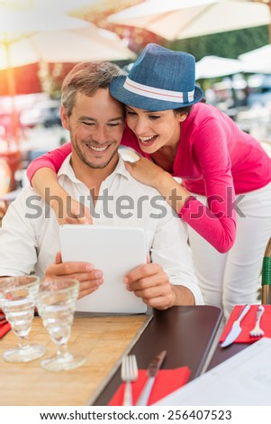 A smiling couple is enjoying drinks at an outside bar table in the city. The man is sitting at the table looking at a digital tablet and the woman is standing close to him. - stock photo