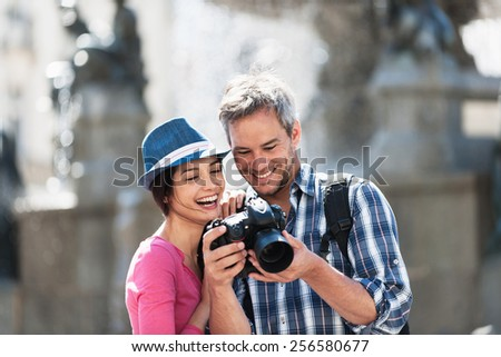 A smiling couple is looking at their photos on the screen of their camera in the city center. The woman is wearing a pink top and a blue hat. The grey hair man with a beard is wearing a backpack. - stock photo
