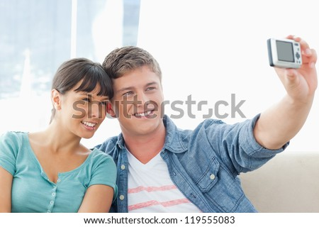 A smiling couple sit on the couch and pose together for a photo - stock photo