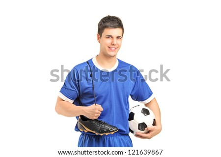 A smiling footballer in sport wear holding a soccer shoes and football isolated on white background - stock photo