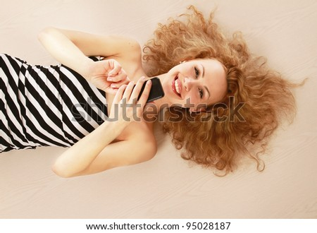 A smiling girl lying on the floor with a mobile phone, isolated on white background - stock photo