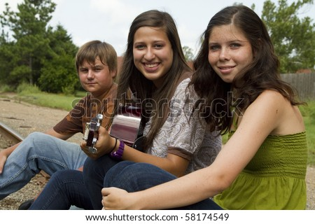 A smiling girl with a guitar sits outside on the railroad tracks with friends. - stock photo