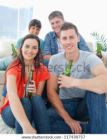 A smiling group of friends as one couple sit on the floor and the other couple sit on the couch with beers - stock photo