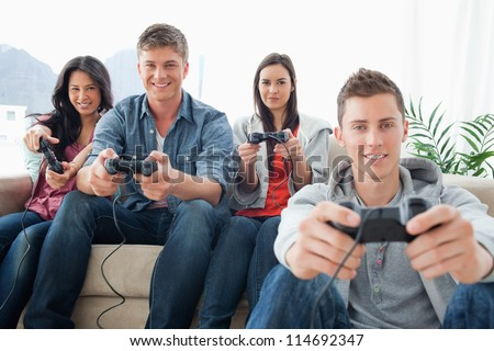A smiling group of friends playing together on a console while looking into the camera - stock photo