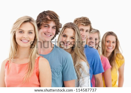 A smiling group standing behind each other at an angle while looking at the camera - stock photo