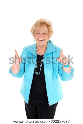 A smiling happy middle age woman in a blue jacket pointing up with her finger, isolated for white background.  - stock photo