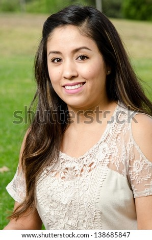 A smiling Hispanic woman in the park. - stock photo