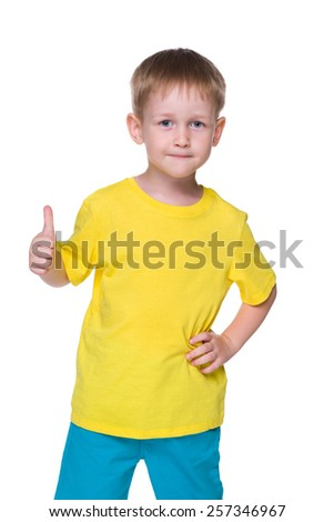 A smiling little boy holds his thumb up on the white background - stock photo