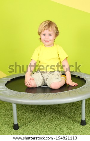 A smiling little boy sitting on a trampoline in a bright room - stock photo
