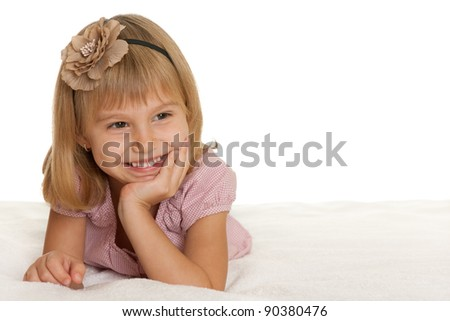 A smiling lying little girl is looking away; isolated on the white background - stock photo