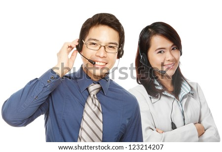 A smiling man and woman wearing headsets - stock photo