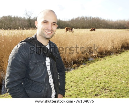 A smiling man standing by a field with cows - stock photo