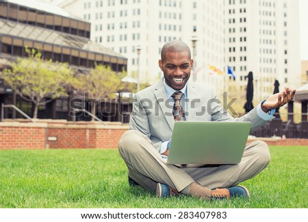 A smiling man with laptop outdoor reading good news email  - stock photo
