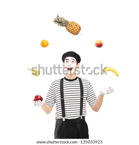 A smiling mime artist juggling fruits isolated against white background - stock photo