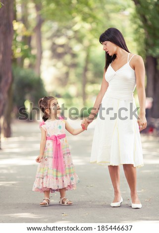 A smiling mother and her daughter are walking in the park and holding hands. - stock photo