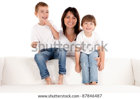 A smiling mother holds her happy pre-school children as they sit laughing on a white sofa. - stock photo