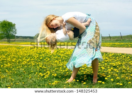 a smiling mother playing and dancing with her happy baby outside in a field of Dandelions - stock photo