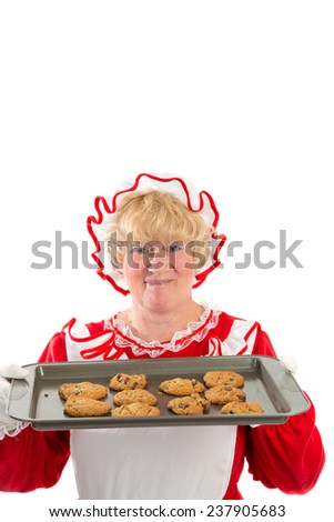 A smiling Mrs Santa holds up a tray of cookies fresh from the oven - stock photo